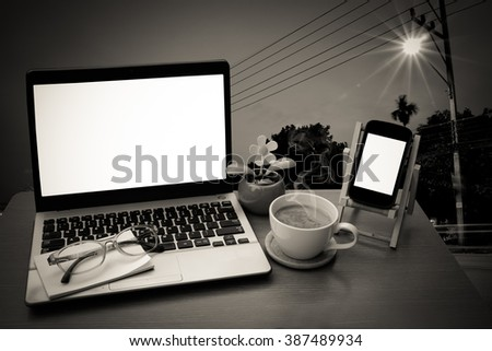 laptop and coffee with traffic light and road background - stock photo