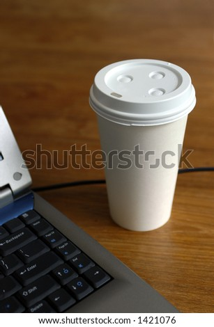 Laptop and coffeecup on wooden table - stock photo