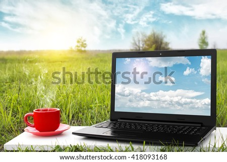 Laptop and cup of hot coffee with blank screen on the background beauty nature, outdoor office. Travel concept. Business idea. Choice of travel. Traveling by airplane. Copy space. Advertising airline. - stock photo