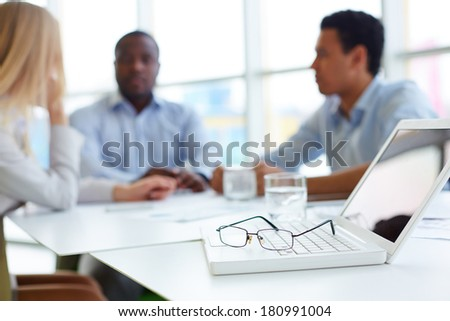 Laptop and eyeglasses on its keypad with group of partners interacting on background - stock photo