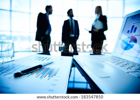 Laptop and financial document with pen at workplace on background of three business partners interacting