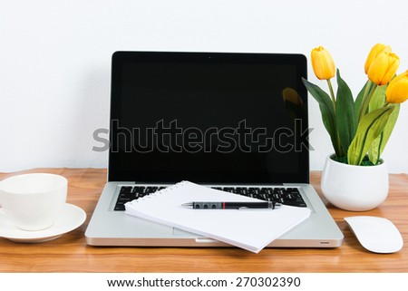 Laptop and flower pot on wooden table on wall background - stock photo