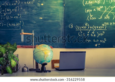 laptop and globe on table of teacher ( Filtered image processed vintage effect. ) - stock photo