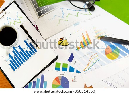 laptop and graphs on the desk.Business Concept