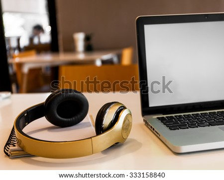 Laptop and Headphone on working desk station. It could be perfect for designers or sound engineer or other related job occupations - stock photo