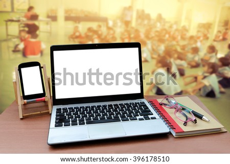 laptop and mobile phone with blur student learning from lecturer background - stock photo