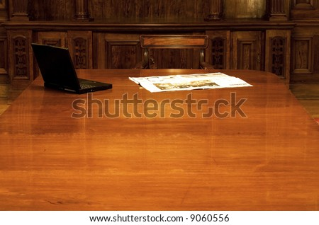 Laptop and newspaper on the desk in old room - stock photo