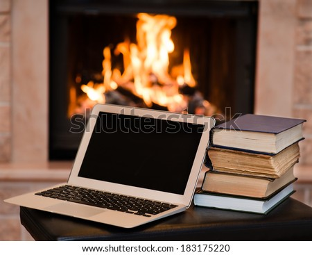 laptop and pile of books against the background of the fireplace - stock photo