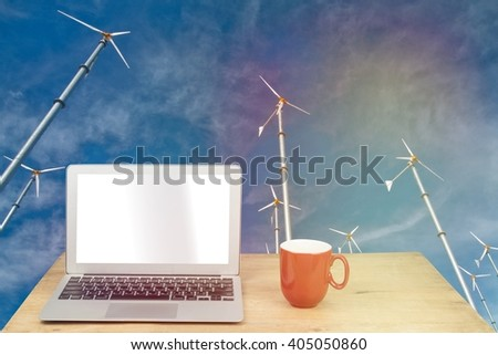 laptop and red mug on wood table with wind turbine - stock photo
