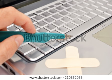 Laptop and scalpel - stock photo