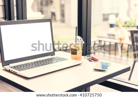 laptop and smart phone, coffee shop background, with soft focus, vintage tone - stock photo