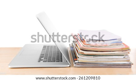 Laptop and stack of magazines on table isolated on white