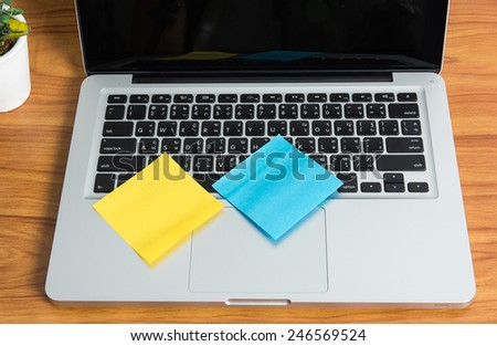 Laptop and stick note on wooden table - stock photo