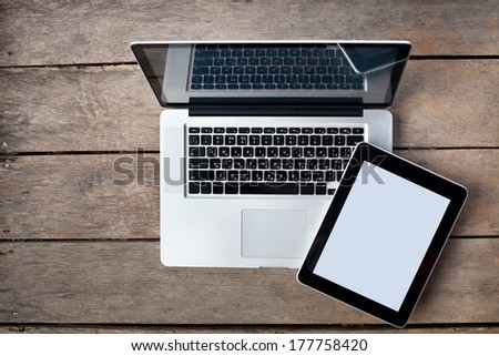 laptop and tablet on old wooden desk - stock photo