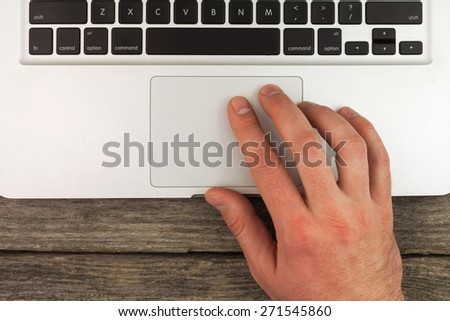 Laptop and typing hand on the wooden desk - stock photo