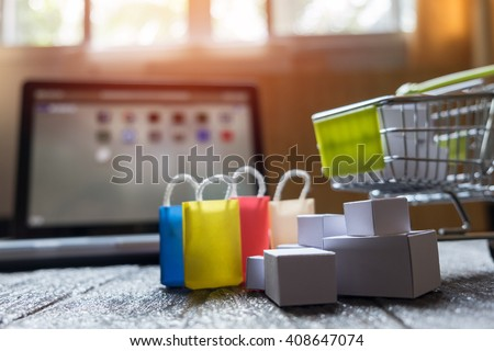 laptop blank screen and hopping cart full of gifts with copyspace, online shopping concept. - stock photo