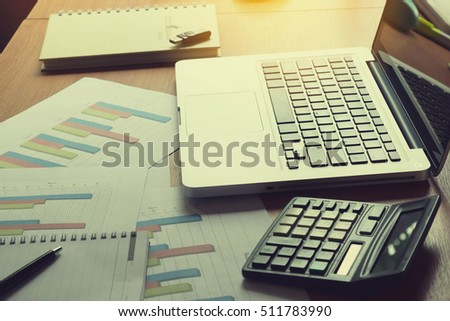Laptop, calculator with financial documents on wooden table