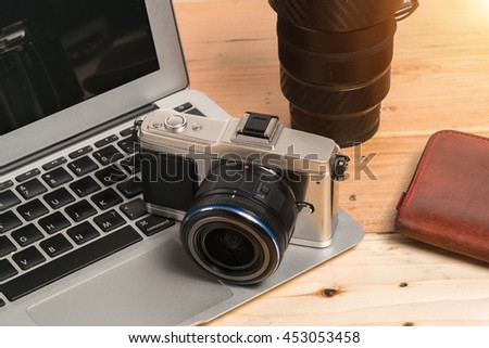 laptop, camera on wooden table