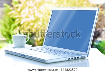 Laptop computer and coffee in the garden - freelance or remote work concept - stock photo