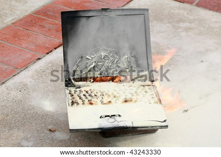 Laptop computer burned in a fire, represents computer damage, loss of data, emergency and more - stock photo