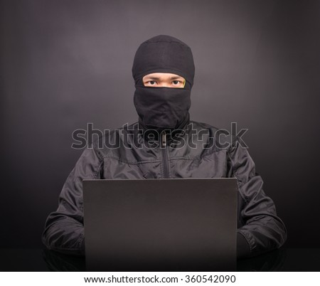 Laptop computer hacker - Male thief stealing data from laptop computer on black background - stock photo