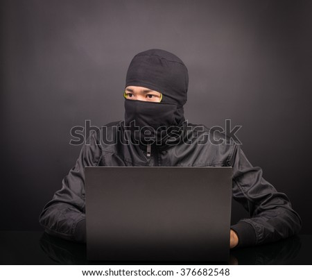 Laptop computer hacker - Male thief stealing data from laptop computer on black background