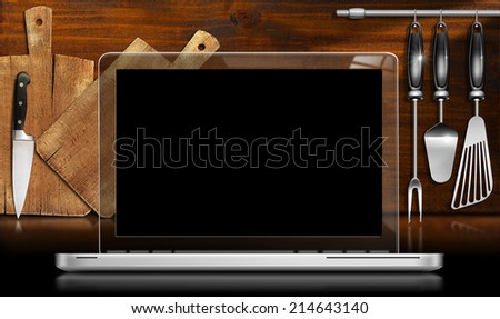 Laptop Computer in the Kitchen / Laptop computer with black and transparent screen in a kitchen with cutting boards and utensils on wooden wall. Template for recipes or food menu - stock photo