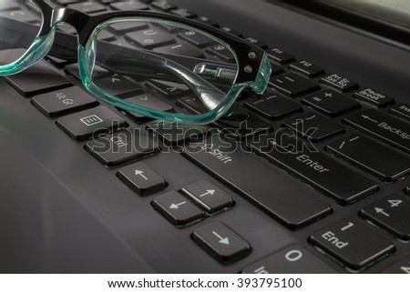 Laptop Computer Keyboard and Spectacles close-up shot at a shallow depth of field