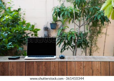 Laptop computer mock up with hard disk on wood texture in garden, left of frame. Relax from work. - stock photo
