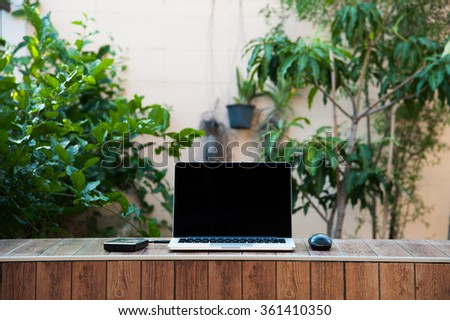Laptop computer mock up with hard disk on wood texture in garden, middle of frame. Relax from work. - stock photo