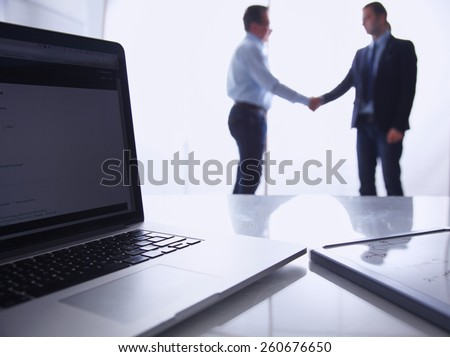 Laptop  computer on  desk , two businesspeople standing in the background - stock photo
