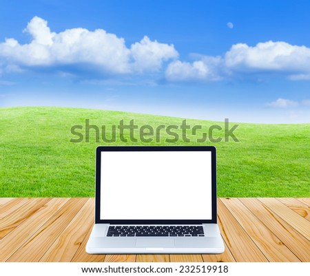 Laptop computer on wooden floor with green fields and blue sky background - stock photo