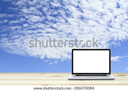 Laptop computer on wooden floor with sky  background. White screen - stock photo
