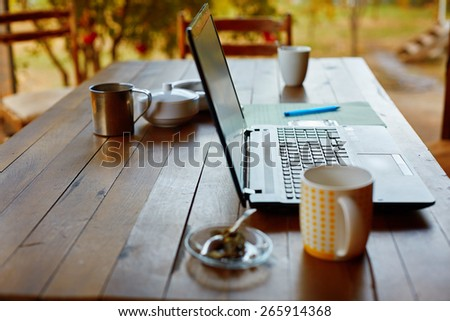 Laptop computer, phone and coffee in the garden - freelance or remote work concept. small depth of field, focus on the keyboard - stock photo