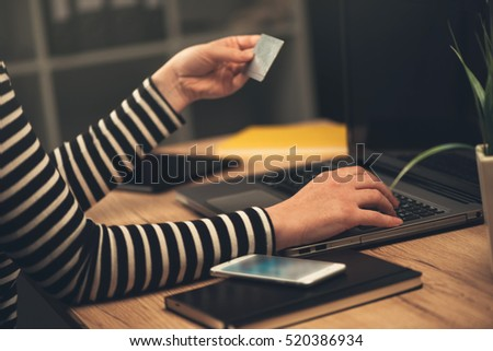 Laptop computer shopping online from office, businesswoman using debit payment card to purchase items on internet, selective focus.