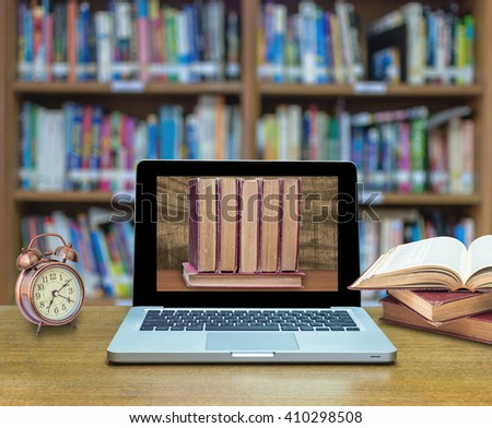 Laptop computer shown the old books in the screen with old books and vintage alarm clock on the wood table in library blurred background, Education concept - stock photo