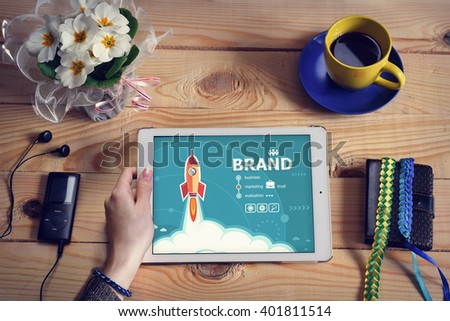 Laptop computer, tablet pc and Brand design concept on wooden office desk with copy space. Brand design concept background with rocket.