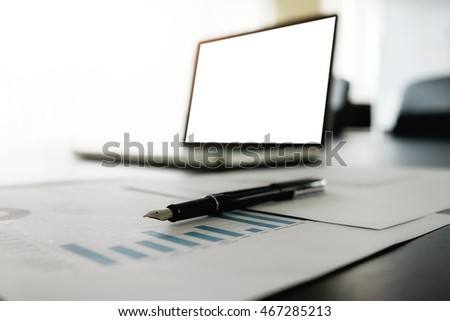 Laptop computer with blank white screen ready for content on wooden desk in meeting with business people discussing the charts and graphs background, selective focus. Business concept.