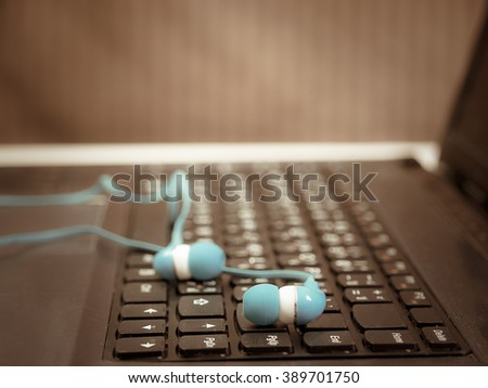Laptop computer with headset on keyboard (vintage) - stock photo