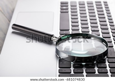 Laptop computer with magnifying glass.