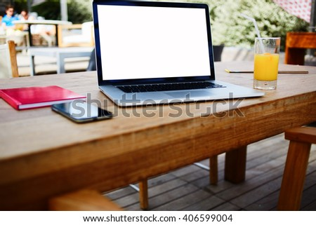 Laptop computer with mock up copy space screen for your advertising text message or promotional content in freelance co-working space. Blank net-book is lying on a table with mobile phone and notepad - stock photo