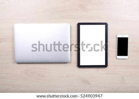 Laptop computer with mockup tablet and smartphone devices on wooden background