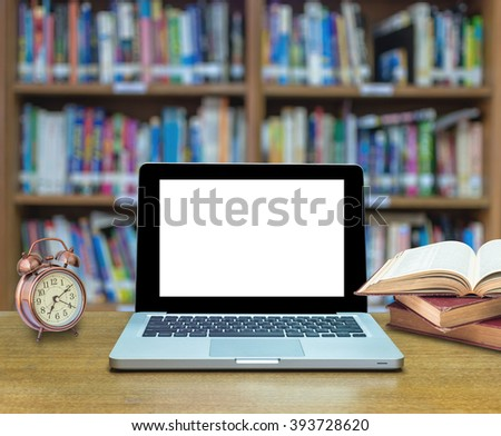 Laptop computer with old books and vintage alarm clock on the wood table in library blurred background, laptop shown empty screen mockup, Education concept - stock photo