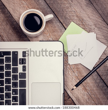 Laptop, Cup of Coffee, Notepaper and Pencil on Vintage Wooden Table. Top View. - stock photo