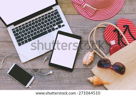 Laptop, digital tablet and smart phone with beach items over wooden background. View from above - stock photo