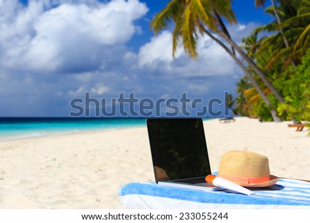 laptop, hat and suncream on chair in tropical beach vacation - stock photo