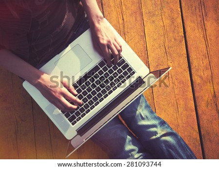 Laptop in girls hands typing and sitting on a wooden floor - stock photo