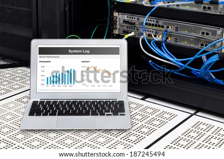 Laptop in network data center, server room. Using for monitoring server computer performance. - stock photo