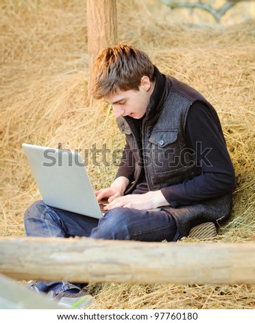 Laptop in the dried grass - stock photo