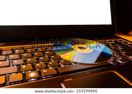 Laptop keyboard with CD - stock photo